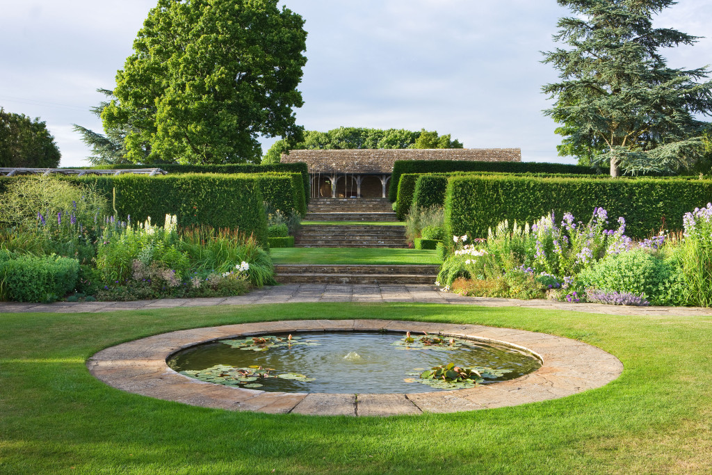 WHATLEY MANOR, WILTSHIRE: CIRCULAR POND IN THE LAWN WITH VIEW THROUGH HEDGES TO THE COTSWOLD STONE LOGGIA