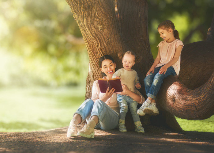 Mother and daughters sitting under the tree on summer lawn. Happy family playing outdoors. Pretty young mom reading a book to her children in the park outside